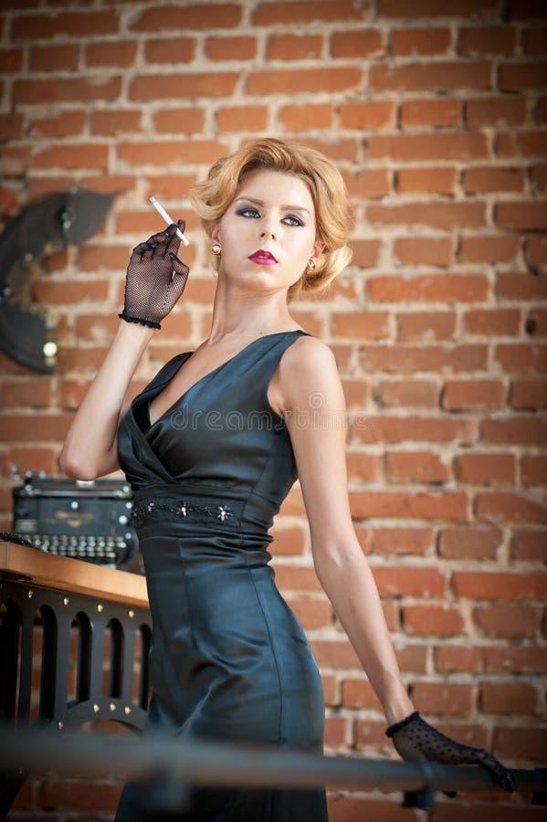Mujer rubia hermosa joven del pelo corto en el vestido negro que fuma un cigarrillo Señora misteriosa romántica elegante con mira fotos de archivo libres de regalías
