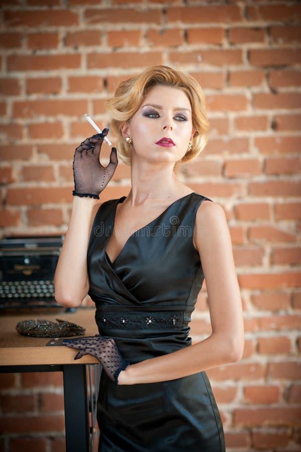 Mujer rubia hermosa joven del pelo corto en el vestido negro que fuma un cigarrillo Señora misteriosa romántica elegante con mira imagenes de archivo