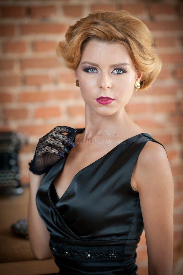 Mujer rubia hermosa joven del pelo corto en la presentación negra del vestido Señora misteriosa romántica elegante con mirada de  foto de archivo libre de regalías