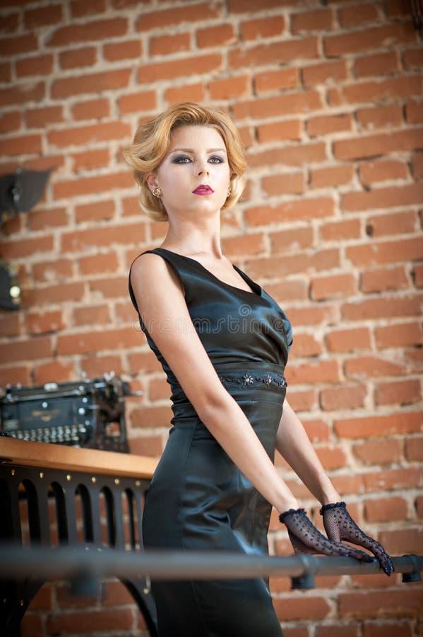 Mujer rubia hermosa joven del pelo corto en la presentación negra del vestido Señora misteriosa romántica elegante con mirada de  fotos de archivo libres de regalías