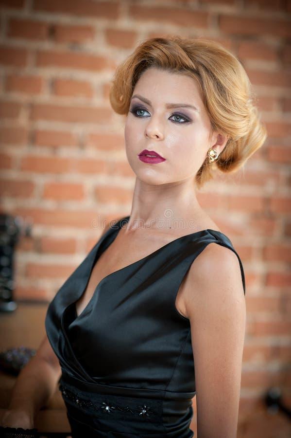 Mujer rubia hermosa joven del pelo corto en la presentación negra del vestido Señora misteriosa romántica elegante con mirada de  fotografía de archivo