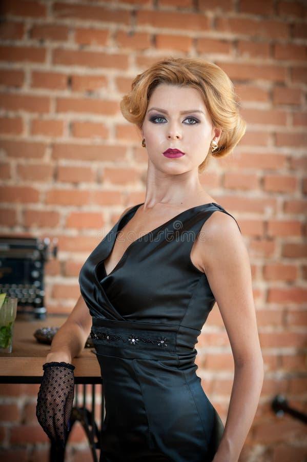 Mujer rubia hermosa joven del pelo corto en la presentación negra del vestido Señora misteriosa romántica elegante con mirada de  imagen de archivo libre de regalías