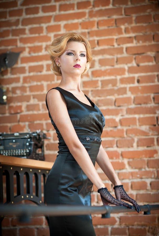 Mujer rubia hermosa joven del pelo corto en la presentación negra del vestido Señora misteriosa romántica elegante con mirada de  foto de archivo