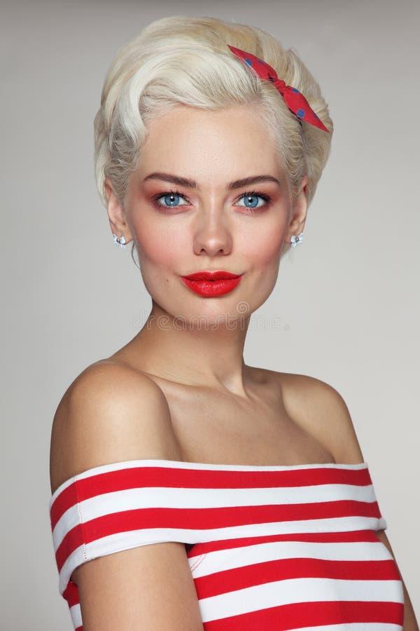 Mujer rubia hermosa joven en top rayado imagenes de archivo