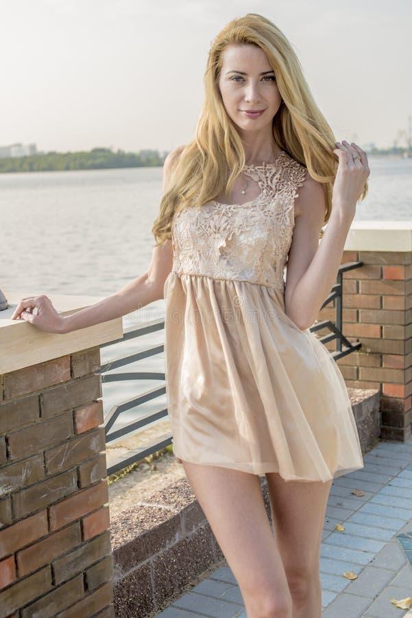 Mujer rubia hermosa joven en un vestido hermoso en un parque del verano imagen de archivo
