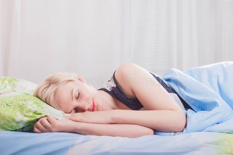 Mujer rubia hermosa joven que duerme en su cama por la mañana imágenes de archivo libres de regalías