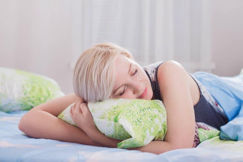 Mujer rubia hermosa joven que duerme en su cama por la mañana imagen de archivo