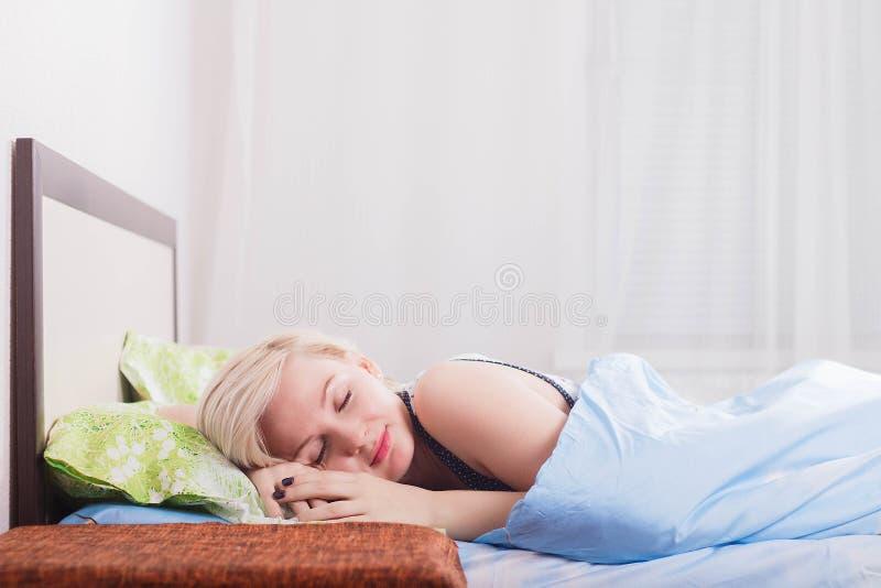 Mujer rubia hermosa joven que duerme en su cama por la mañana fotos de archivo libres de regalías