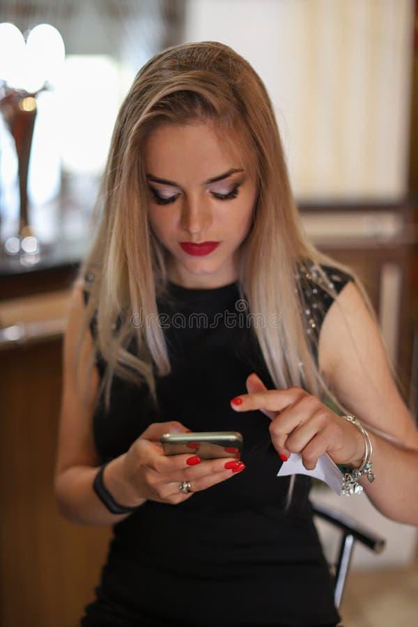 Mujer rubia hermosa joven que escribe o que lee mensajes del SMS en línea en un teléfono elegante en un restaurante El usar elega foto de archivo libre de regalías