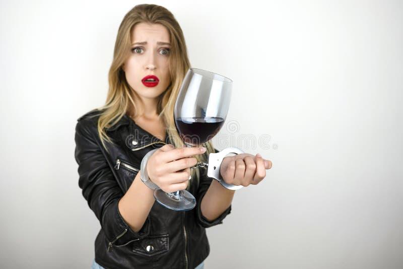 Mujer rubia hermosa joven que lleva las bebidas negras vino de la chaqueta de cuero y siendo arrestado y esposado en aislado imagenes de archivo