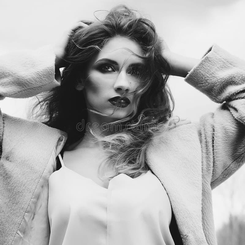 Mujer rubia hermosa joven que presenta en capa al aire libre imagen de archivo