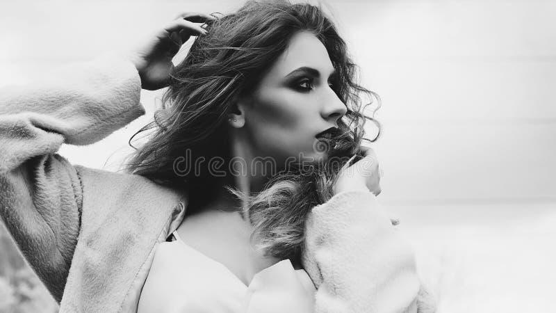 Mujer rubia hermosa joven que presenta en capa al aire libre fotografía de archivo