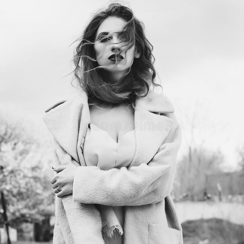 Mujer rubia hermosa joven que presenta en capa al aire libre imagen de archivo libre de regalías