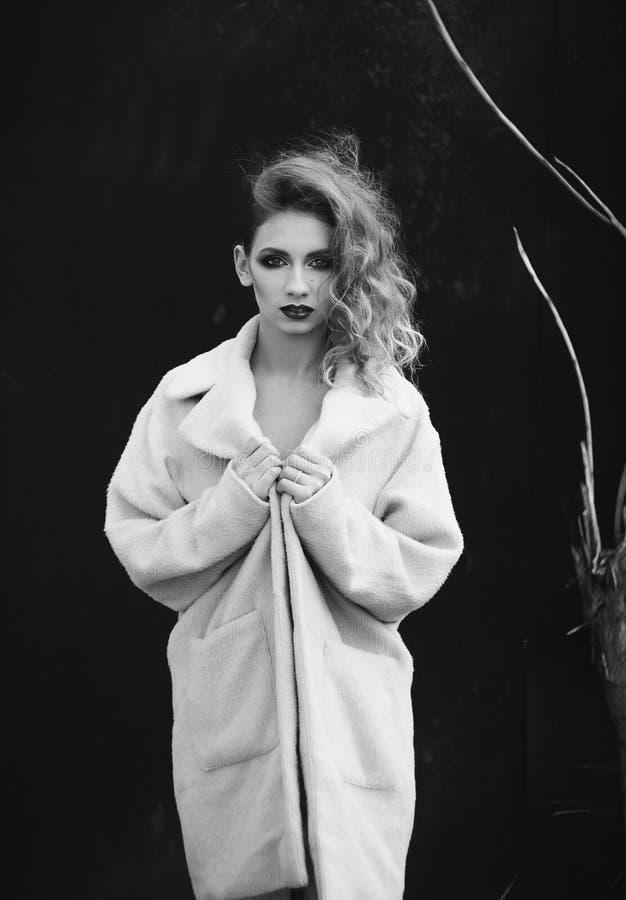 Mujer rubia hermosa joven que presenta en capa al aire libre foto de archivo