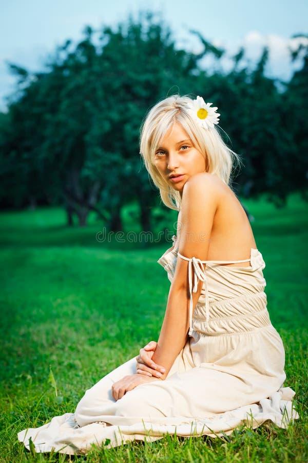 Mujer rubia hermosa joven que se sienta en hierba imagenes de archivo
