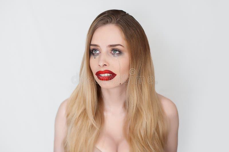 Mujer rubia hermosa que llora con el lápiz labial rojo fotografía de archivo