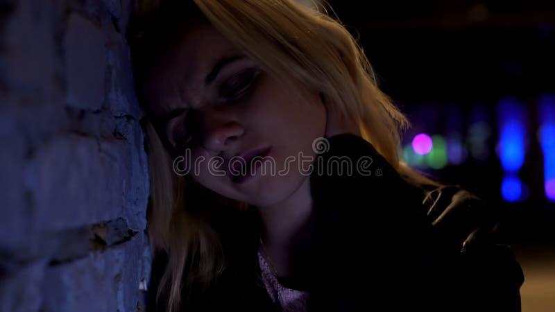 Mujer rubia hermosa que llora, inclinándose en la pared, sufriendo después de primer de la desintegración fotos de archivo libres de regalías