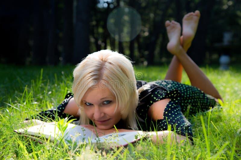 Mujer rubia hermosa que mira para arriba de la lectura fotos de archivo libres de regalías