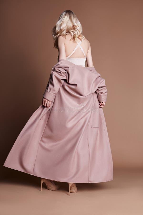Mujer rubia hermosa que presenta en una capa rosada en un fondo beige Ropa del desfile de moda, mujer con la figura perfecta, pel fotografía de archivo libre de regalías