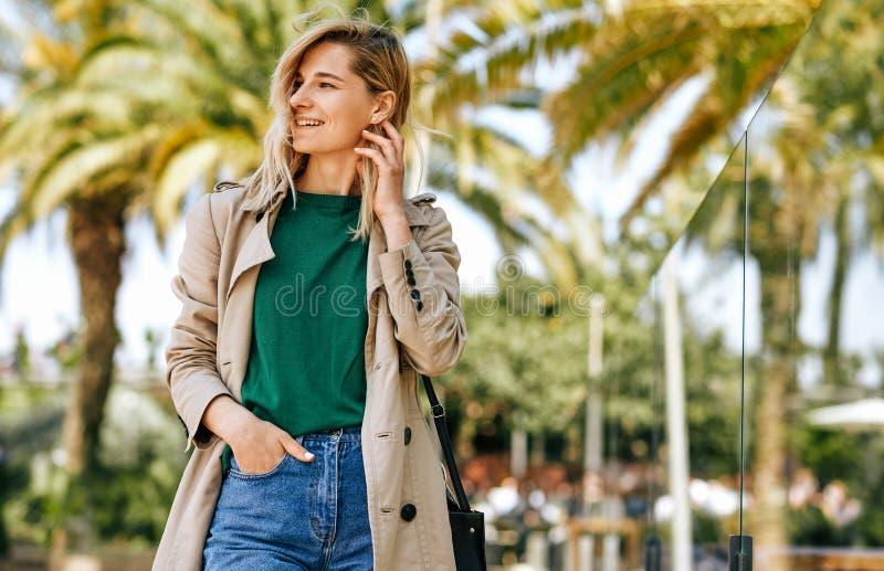 Mujer rubia hermosa que sonríe ampliamente, mirando lejos, durante vacaciones El caminar femenino atractivo en la calle de la ciu fotos de archivo libres de regalías