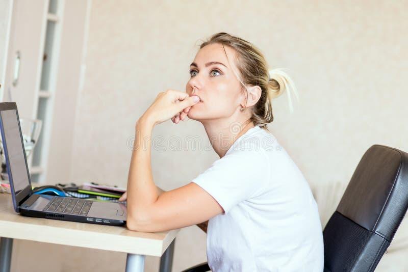 Mujer rubia hermosa que trabaja en el ordenador portátil en casa Ella es pensativa y centrada en trabajo Independiente, concepto  imágenes de archivo libres de regalías