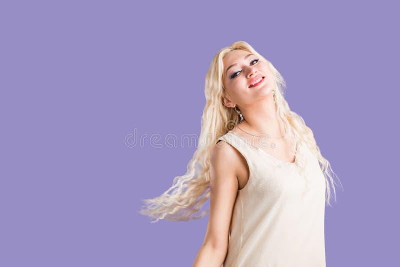 Mujer rubia hermosa sonriente en el fondo violeta imagen de archivo