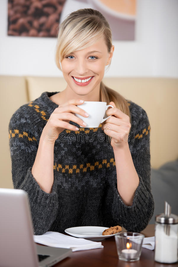 Mujer rubia hermosa sonriente que bebe un café fotos de archivo