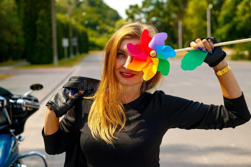 Mujer rubia hermosa sonriente que lleva a cabo un aire libre del molinillo de viento el día de fiesta imagen de archivo