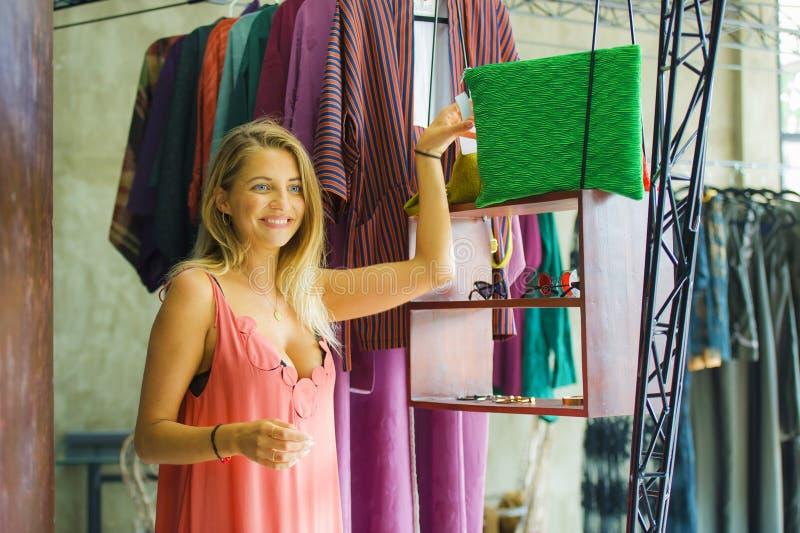 Mujer rubia hermosa y feliz joven que disfruta de hacer compras probando la ropa en el cheerf sonriente del vintage y de la tiend fotos de archivo