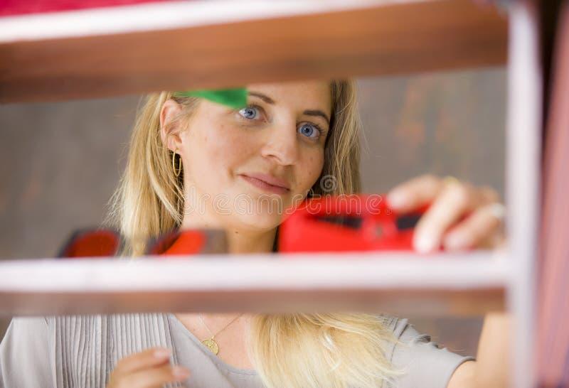 Mujer rubia hermosa y feliz joven que disfruta de hacer compras probando la ropa y las gafas de sol en el vintage y la tienda fre foto de archivo libre de regalías