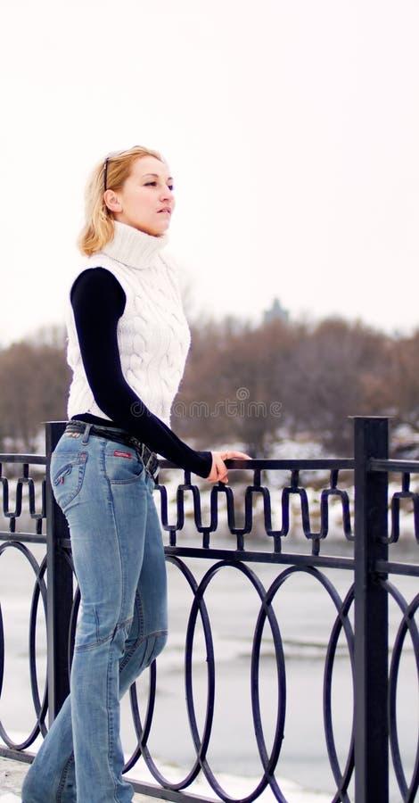 Mujer rubia joven arropada en el suéter blanco foto de archivo libre de regalías