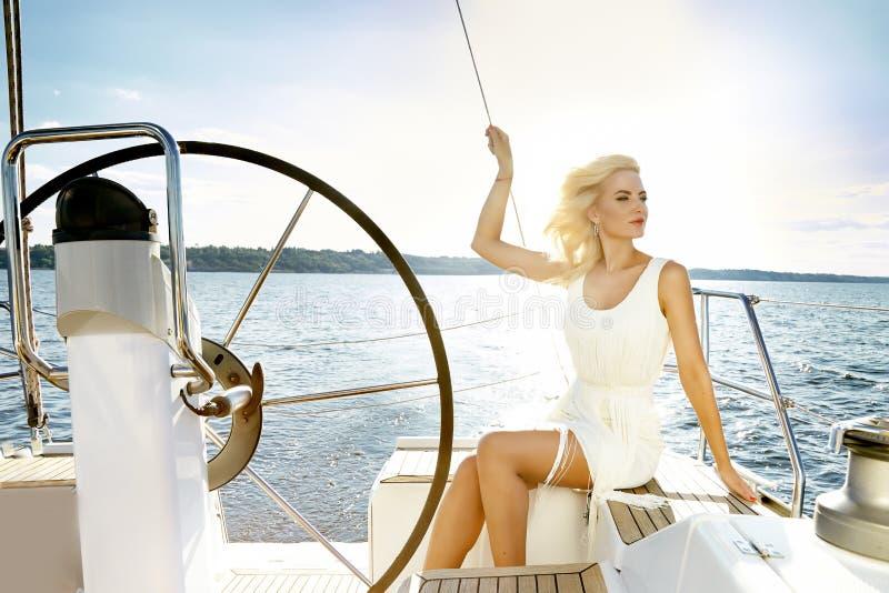 Mujer rubia joven atractiva hermosa, montando un barco en el agua, itinerario, maquillaje hermoso, ropa, verano, sol, cuerpo perf foto de archivo libre de regalías