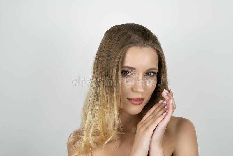 Mujer rubia joven atractiva que pone una mano en otras manos que se sostienen cerca de cierre del hombro encima del fondo blanco  fotografía de archivo