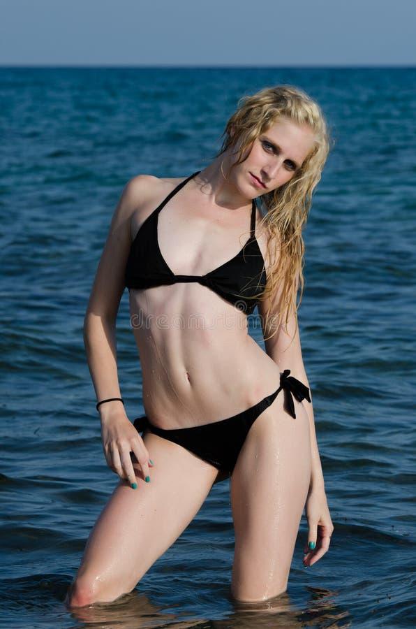 Mujer rubia joven atractiva que presenta en el mar foto de archivo
