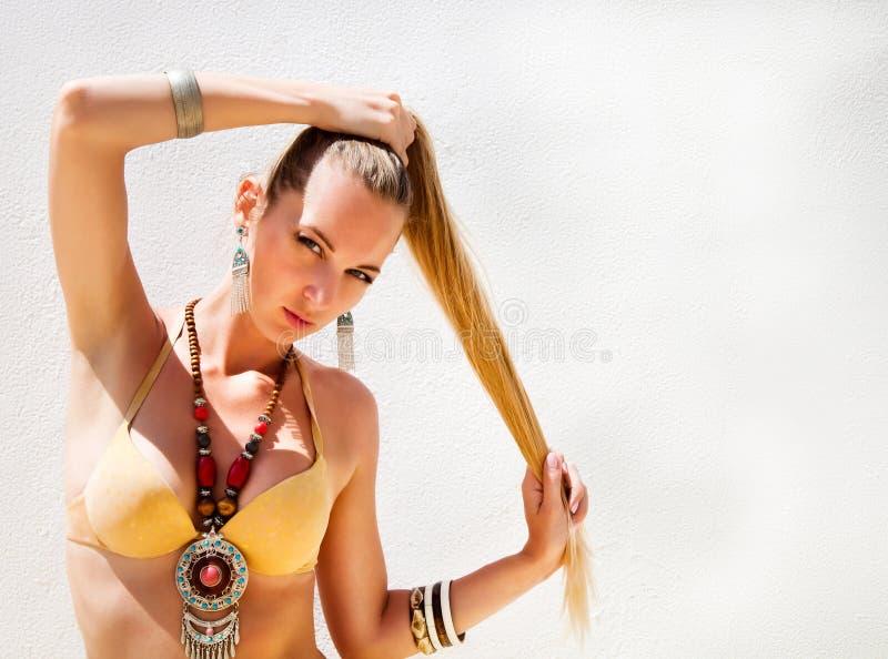 Mujer rubia joven atractiva que presenta en un bikini del oro foto de archivo libre de regalías