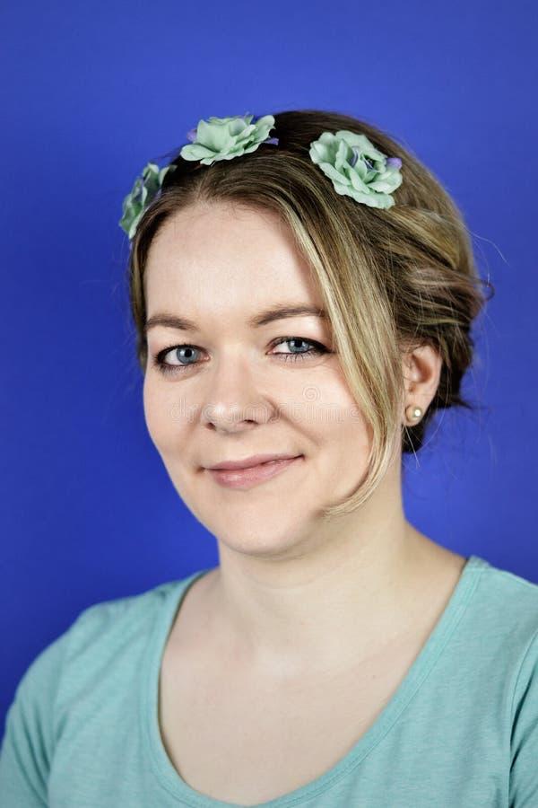 Mujer rubia joven con el pelo del updo y las flores ci?nicas imagen de archivo libre de regalías