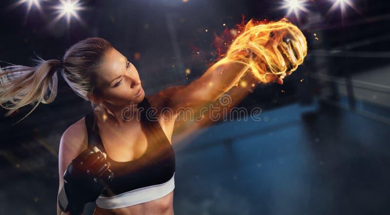 Mujer rubia joven con el puño del fuego imagenes de archivo