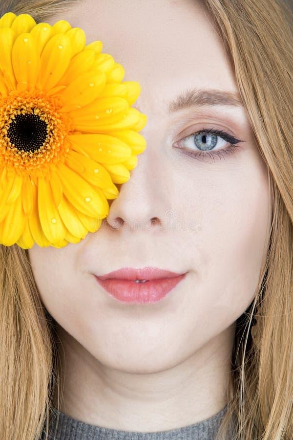 Mujer rubia joven con la flor en su mano imagen de archivo