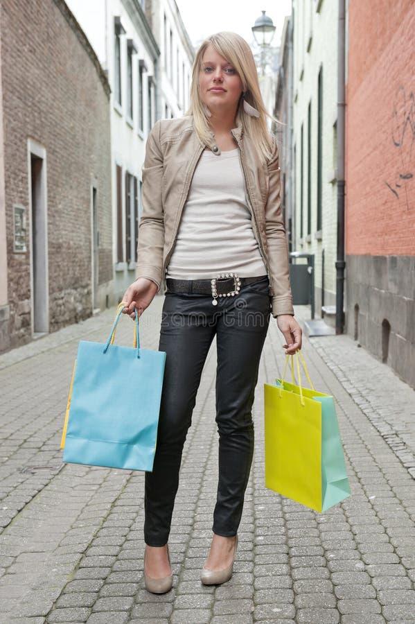 Mujer rubia joven con los bolsos de compras imagen de archivo
