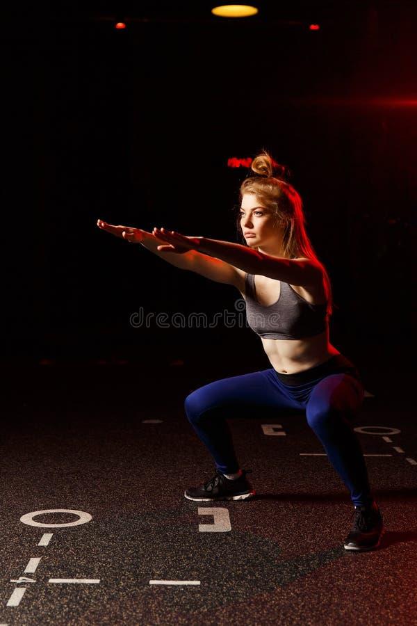 Mujer rubia joven con los brazos extendidos que hacen estocadas en gimnasio fotos de archivo libres de regalías