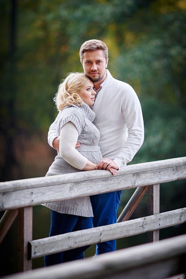 Mujer rubia joven con su marido en el parque en el puente fotografía de archivo