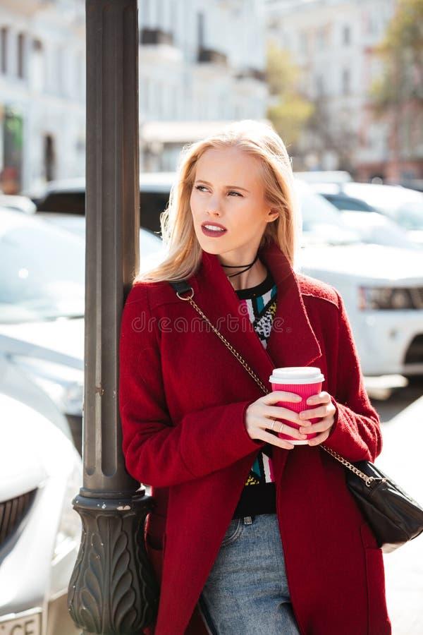 Mujer rubia joven de la moda seria que camina al aire libre fotografía de archivo libre de regalías
