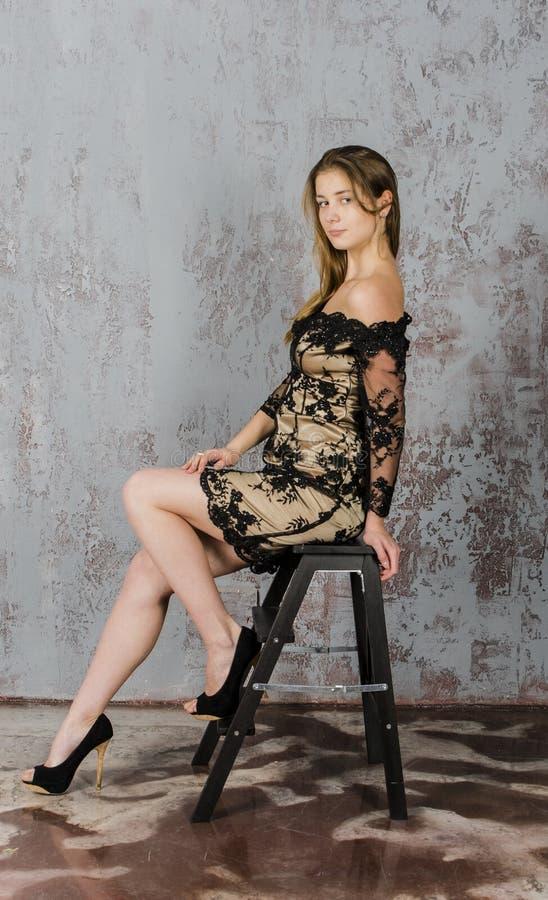 Mujer rubia joven de pelo largo hermosa con una figura delgada en un oro y un mini vestido negro foto de archivo libre de regalías