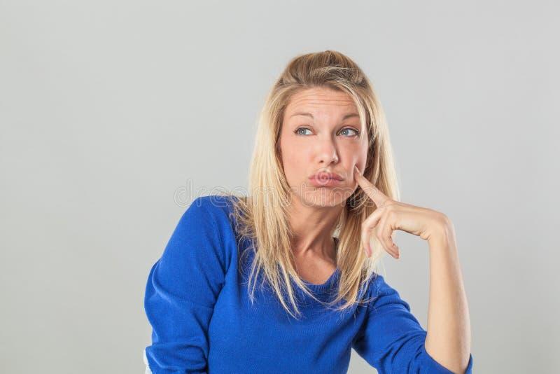 Mujer rubia joven de pensamiento que mira lejos con índice en mejilla imagen de archivo