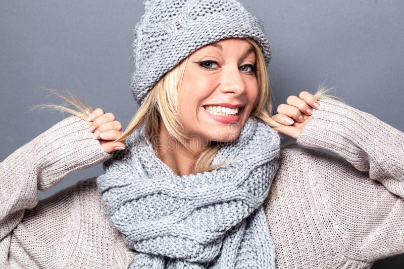 Mujer rubia joven del invierno femenino que sonríe y que juega con el pelo imagenes de archivo