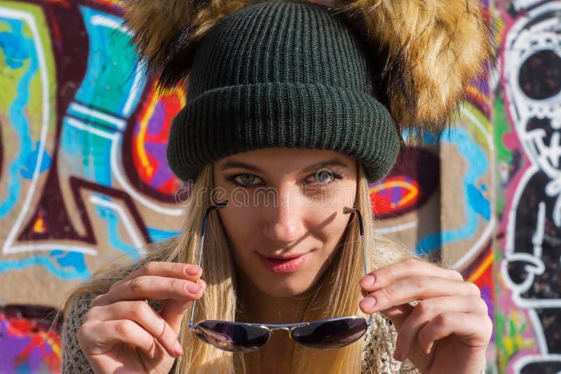 Mujer rubia joven divertida en el sombrero y las gafas de sol que miran la cámara fotos de archivo