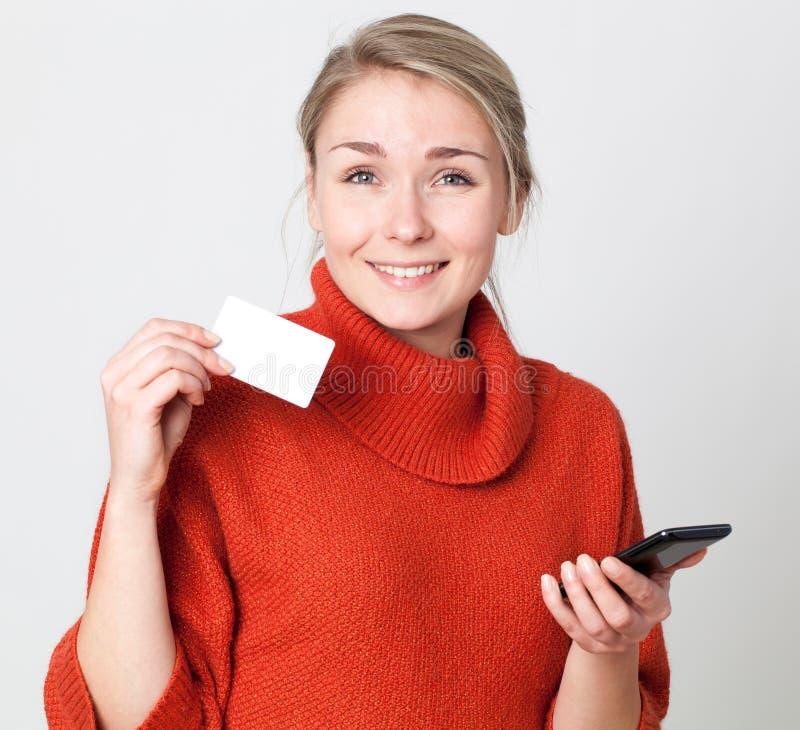 Mujer rubia joven emocionada que hace una transacción de las compras en línea imagen de archivo libre de regalías