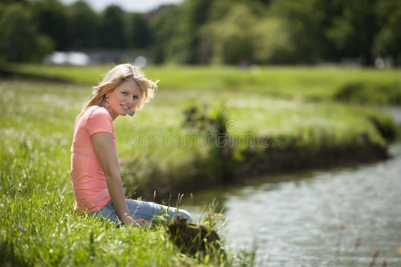 Mujer rubia joven en blanco asentada en el lago fotografía de archivo libre de regalías