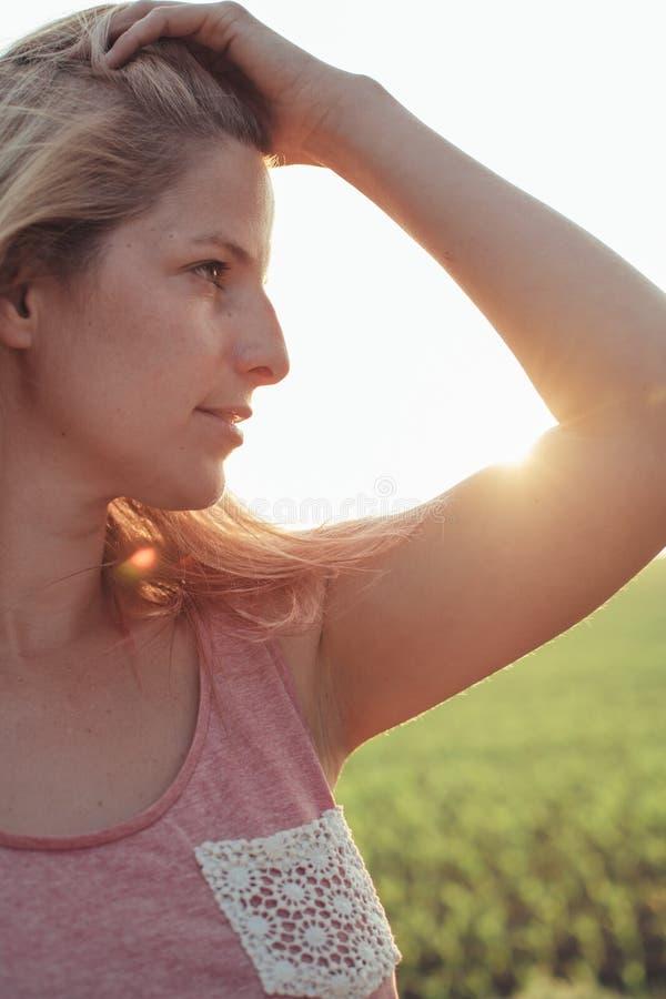 Mujer rubia joven en la puesta del sol fotografía de archivo libre de regalías