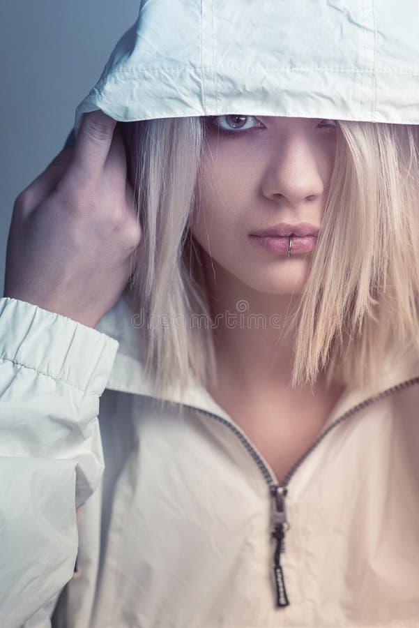 Mujer rubia joven en la sudadera con capucha blanca imágenes de archivo libres de regalías